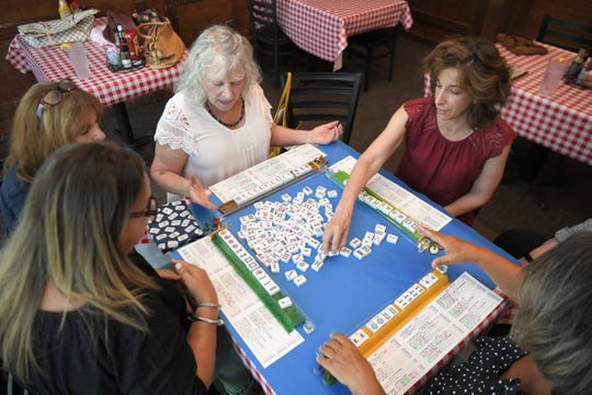 Michelle Tishler, right, leads a game  of mahjong with friends at Corner Pub in the Woods in Bellevue on Sept. 4, 2019.  Tishler, who learned mahjong from the women in her family, also teaches the game.
