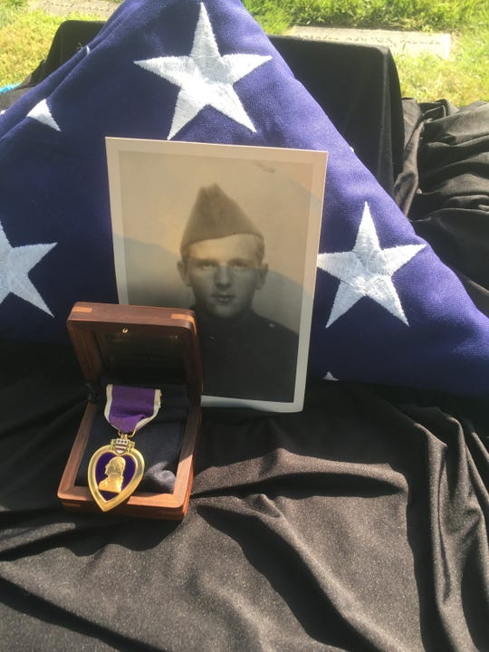 A photo of Staff Sergeant Joseph Armbrust and his recently identified Purple Heart medal awarded him for service during D-Day. The flag is the one presented his family at his 1999 funeral.