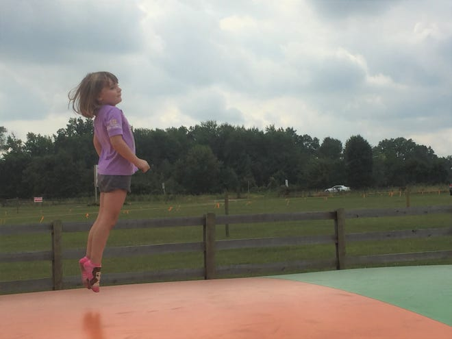 Sofie Loughry, 5, bounces on the bounce pillow at Van Buren Acres on Sept. 7.