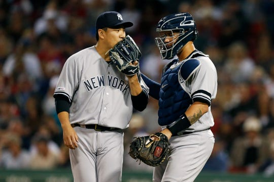 New York Yankees' Masahiro Tanaka, left, talks with Gary Sanchez during the first inning of a baseball game against the Boston Red Sox in Boston, Sunday, Sept. 8, 2019. (AP Photo/Michael Dwyer)