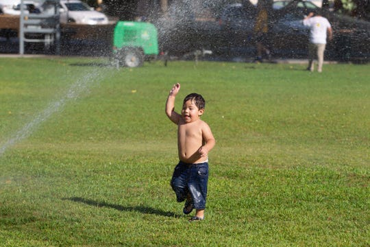 Ivan Ramirez, 2, enjoys the cool water of the sprinklers on a hot day at the Monuments to Main Street kick-off fiesta held at Klein Park on Sunday, Sept. 8, 2019.