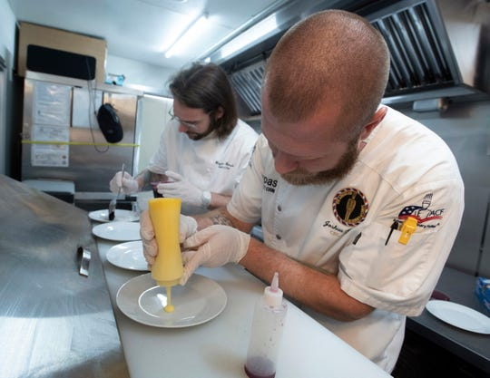 From left, Blayne Barsuhn, Pensacola Country Club sous chef, and Joshua Spiess, owner of the Arepas food truck, practice their plating skills Monday. The team will compete in the World Food Championships next month in Dallas.
