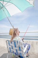 Floriene Henning sits in the shade of her umbrella to avoid the extreme heat as she fishes off the pier in Pensacola on Monday.