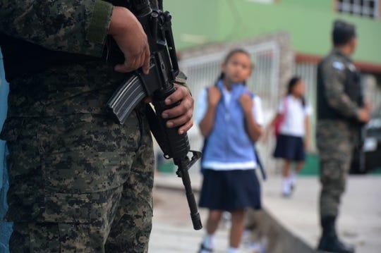 Un elemento de la seguridad nacional vigila afuera de una escuela.