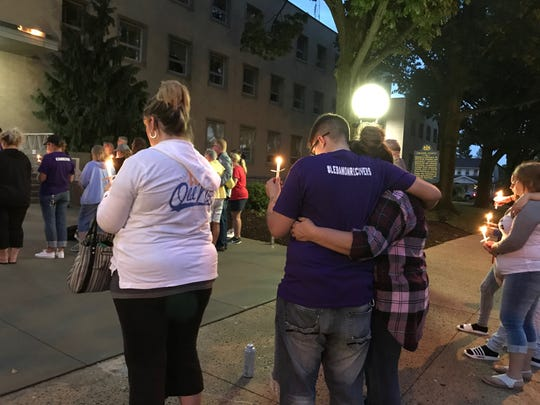 People embrace at a vigil for those lost to overdoses in late August in front of the municipal building in Lebanon.