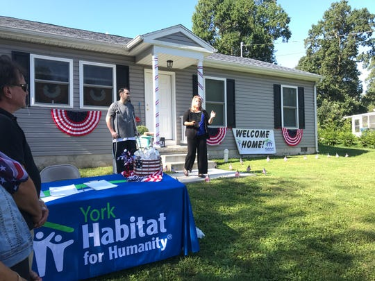 David Hummer, left, is a U.S. veteran who moved into a rancher built by York Habitat for Humanity. Tammi Morris, right, executive director of the nonprofit, spoke to a crowd during a dedication on Saturday.