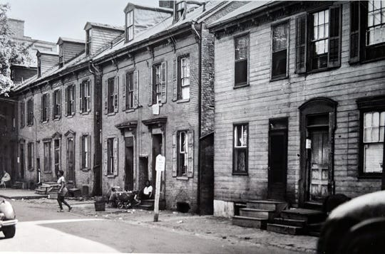 People walk or sit along Freys Avenue, between East King and East Princess Streets. At the time of the race riots, people still lived here. High-rise apartments replaced this old housing in the early 1970s.