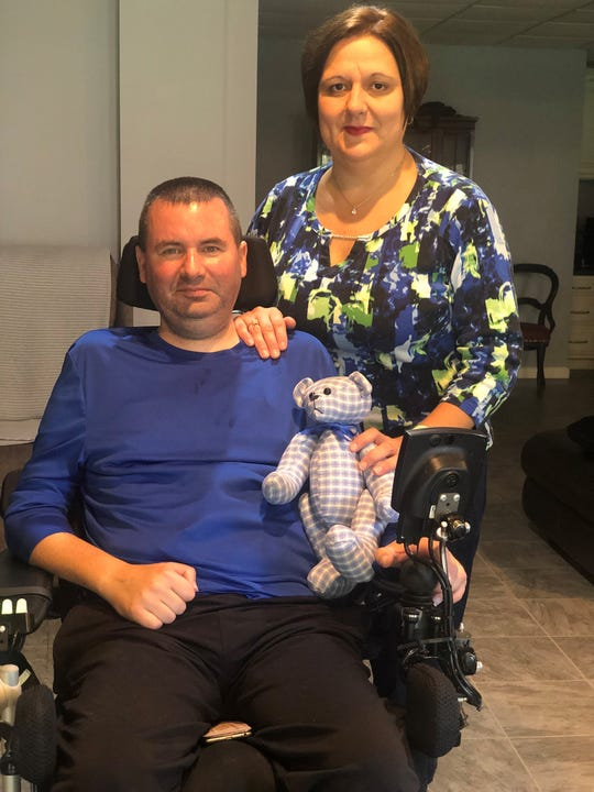 Jeff and Kelley Hottle hold the bear Jeff asked a friend to make for his wife. They live in Chambersburg in an apartment created in the basement of Kelley's parents' home.