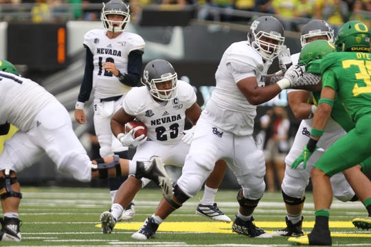Wolf Pack running back Kelton Moore (23) looks for running room against Oregon Ducks defense in the first half at Autzen Stadium.