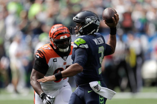 Seattle Seahawks quarterback Russell Wilson, right, passes as Cincinnati Bengals defensive tackle Geno Atkins, left, closes in during the first half of an NFL football game, Sept. 8, 2019, in Seattle.