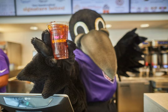 The Baltimore Ravens mascot, Poe, holds an Dunkin' iced coffee. After the Ravens' Sunday win against the Miami Dolphins, Dunkin' is offering free coffee to customers in the Baltimore and Salisbury regions.