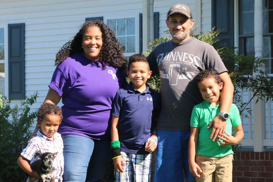 Tara and John Kearns pose with their three children Avery, 4 (with dog Sweet Pea), Trey, 9, and Grayson, 7, Thursday, Aug. 29, 2019, in front of their home in Eden, Maryland.  Trey was born with the rare genetic disease Progressive Familial Intrahepatic Cholestasis, or PFIC, which typically leads to liver failure before adulthood. Tara's response to the family's search for an understanding community of others experiencing PFIC was to become co-leader of the advocacy group PFIC Network, which brings together PFIC families from around the world.