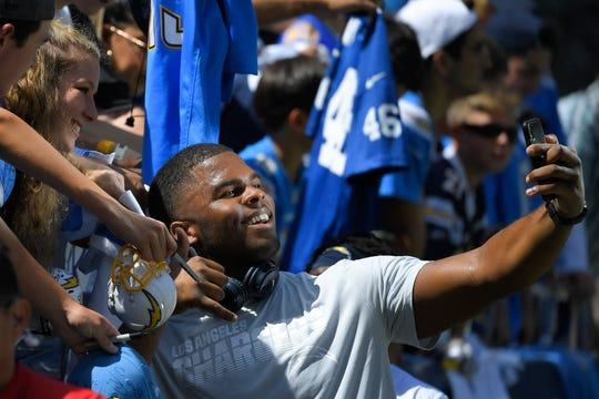 Los Angeles Chargers defensive tackle Jerry Tillery takes a photo with a fan before an NFL football game against the Indianapolis Colts on Sunday.