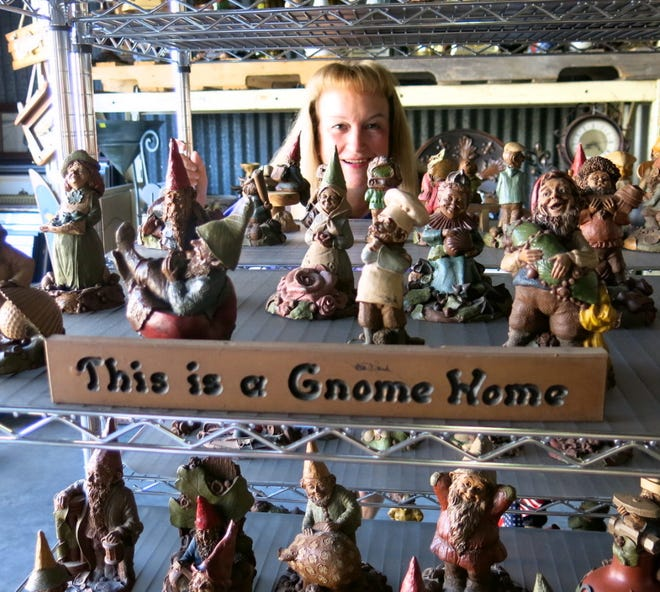 Rummage Sale Chief Kim Hoover peeks through a display of gnomes being shown for the fund raiser.