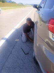 Mady Rankin, of Ozark, took a photo of OTC officer Aaron Powell as he changed her tire Wednesday on Interstate 44 near the OTC Lebanon Center.