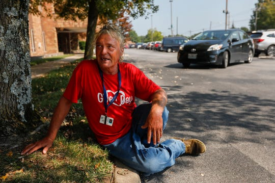 Charlie Orman sits on the sidewalk as his Burrell case worker Linda Hamer pulls her car around to pick him up outside of the Fremont Clinic at Mercy Hospital on Thursday, Sep. 5, 2019.