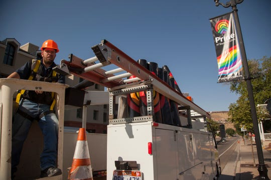 Workers place pride banners on St. George Boulevard in anticipation of Pride Week Monday, Sept. 9, 2019.