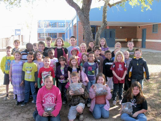 Ft. Braden Elementary students hold bags of acorns they collected for orphaned baby squirrels at St. Francis Wildlife.
