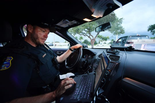 Stuart Police Officer Ken Leedham searches the history on the driver he pulled over after witnessing him turn onto U.S. 1 and striking the sidewalk south of Roosevelt Bridge on Aug. 27, 2019, in Stuart. Leedham later noted that in addition to operating the vehicle with no insurance and while his license was suspended, the driver was not wearing a seat belt.