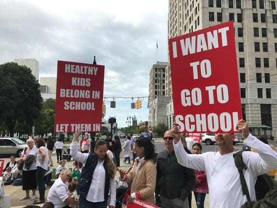 A protestor holds a sign in opposition to a new law that bans religious exemptions from vaccinations during a rally outside the state Education Building in Albany on Sept. 9, 2019.
