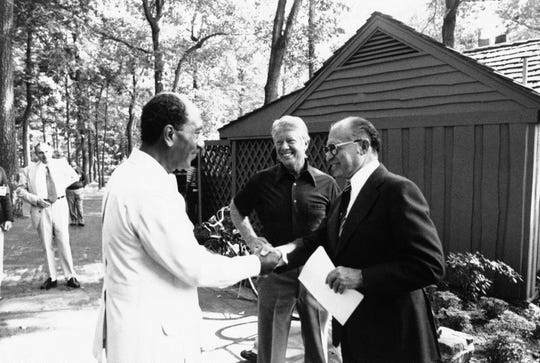 ORG XMIT: APHS359015 In this Official White House photo, Egyptian President Anwar Sadat, left, shakes hands with Israeli Prime Minister Menachem Begin as President Jimmy Carter looks on outside a lodge at Camp David, Maryland on Sept. 7, 1978. (AP Photo/Official White House Photo) NO SALES [Via MerlinFTP Drop]