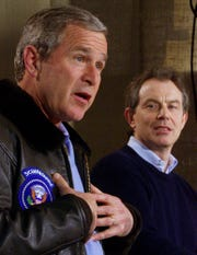 President Bush answers a question as British Prime Minister Tony Blair looks on during a press conference in Thurmont, Md., outside Camp David Friday, Feb. 23, 2001. (AP Photo/Doug Mills) ORG XMIT: DSM124
