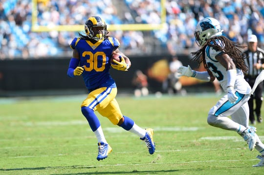 Los Angeles Rams running back Todd Gurley (30) runs as Carolina Panthers defensive back Tre Boston (33) defends in the fourth quarter at Bank of America Stadium.
