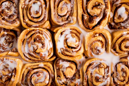 Sweet potato pecan rolls covered in frosting in a pan.