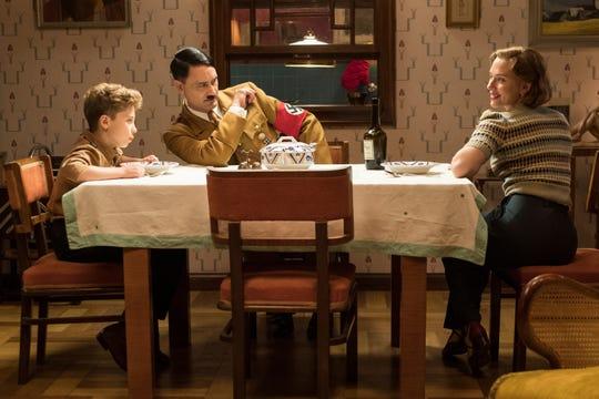 "Jojo (Roman Griffin Davis) has dinner with his imaginary friend Adolf (Taika Waititi), and his mother Rosie (Scarlet Johansson) in the World War II satire ""Jojo Rabbit."""