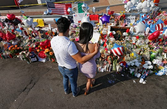 Mourner stand near a display for victims of a mass shooting at an El Paso, Texas, Walmart store, in this file photo from Aug. 7.