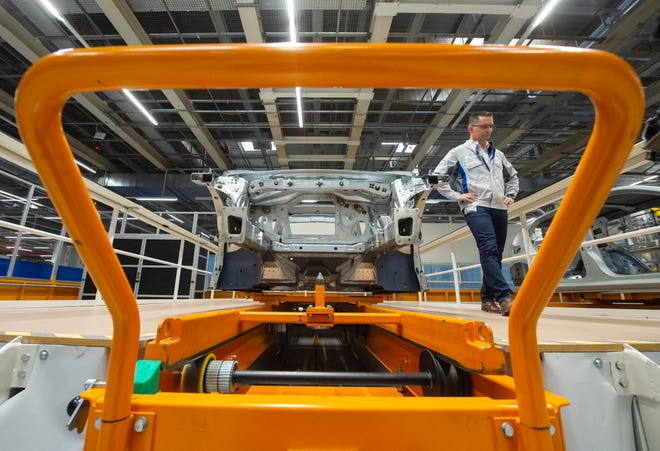 In this Tuesday, May 14, 2019 file photo, Heiko Roesch, head of body construction, walks besides the new electric 'ID.3' car body during a press tour at the plant of the German manufacturer Volkswagen AG (VW) in Zwickau, Germany.