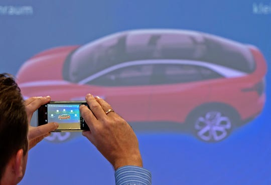In this Tuesday, May 14, 2019 file photo, a journalist takes photographs during a presentation of the new electric 'ID.3' car at a press tour of the plant of the German manufacturer Volkswagen AG (VW) in Zwickau, Germany.