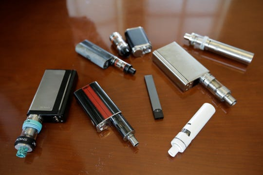 This April 2018 file photo shows vaping devices, including a Juul, center, that were confiscated from students at a high school in Marshfield, Mass.