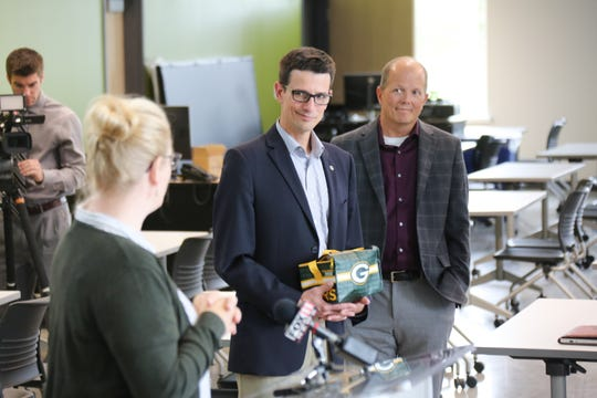 Aaron Popkey, director of public affairs for the Green Bay Packers, holds a soil sample from a practice field for the Tiny Earth kickoff at UW-Green Bay Monday.