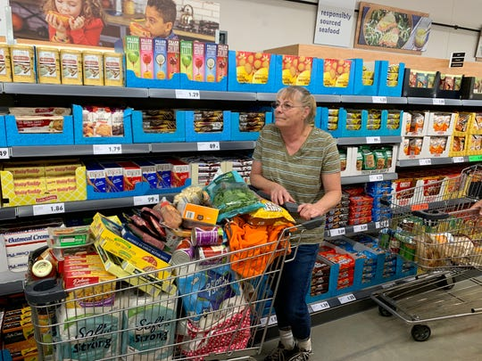 Lacey resident Cindy Heiart has a full cart at Lidl's grand opening.