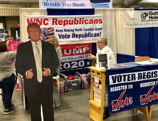 Fremont Brown, right, mans the Buncombe County Republican booth at the Mountain State Fair on Sept. 9, 2019. Brown says the booth has not given out any inflatable items at all, and definitely not any inflatable rifles.