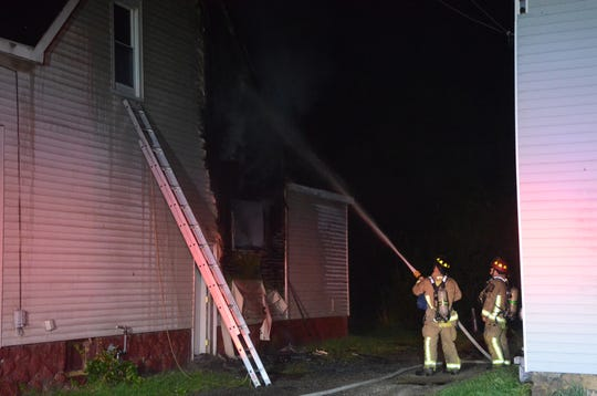 Firefighters fight a fire on Cherry Street Tuesday.