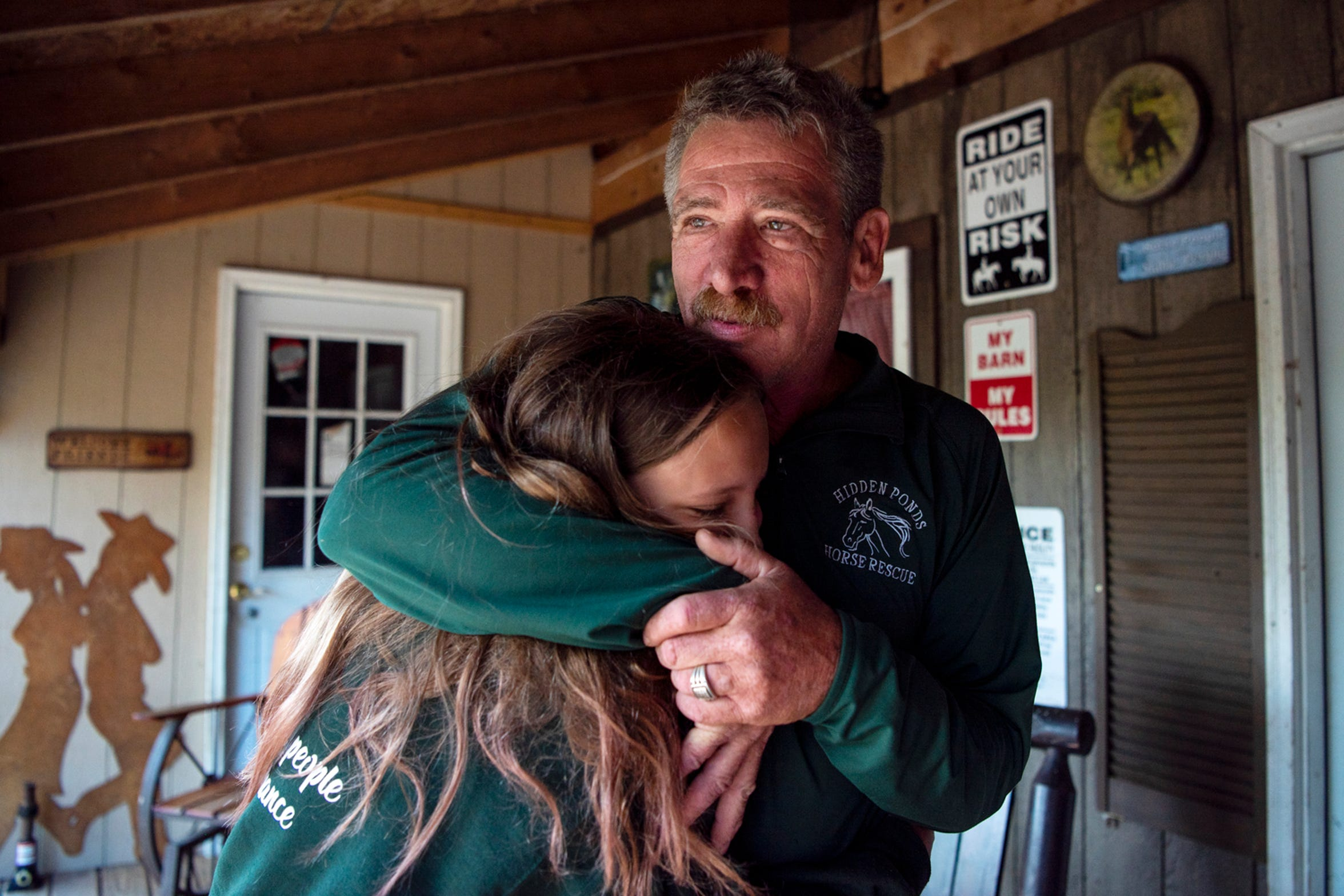 Jeff Friend and Hadassah Bloom, 12, embrace on Saturday, Sept. 7, 2019 at Hidden Ponds Horse Rescue in Coldwater, Mich. Students refer to Friend, owner of Hidden Ponds, as Grandpa Jeff.