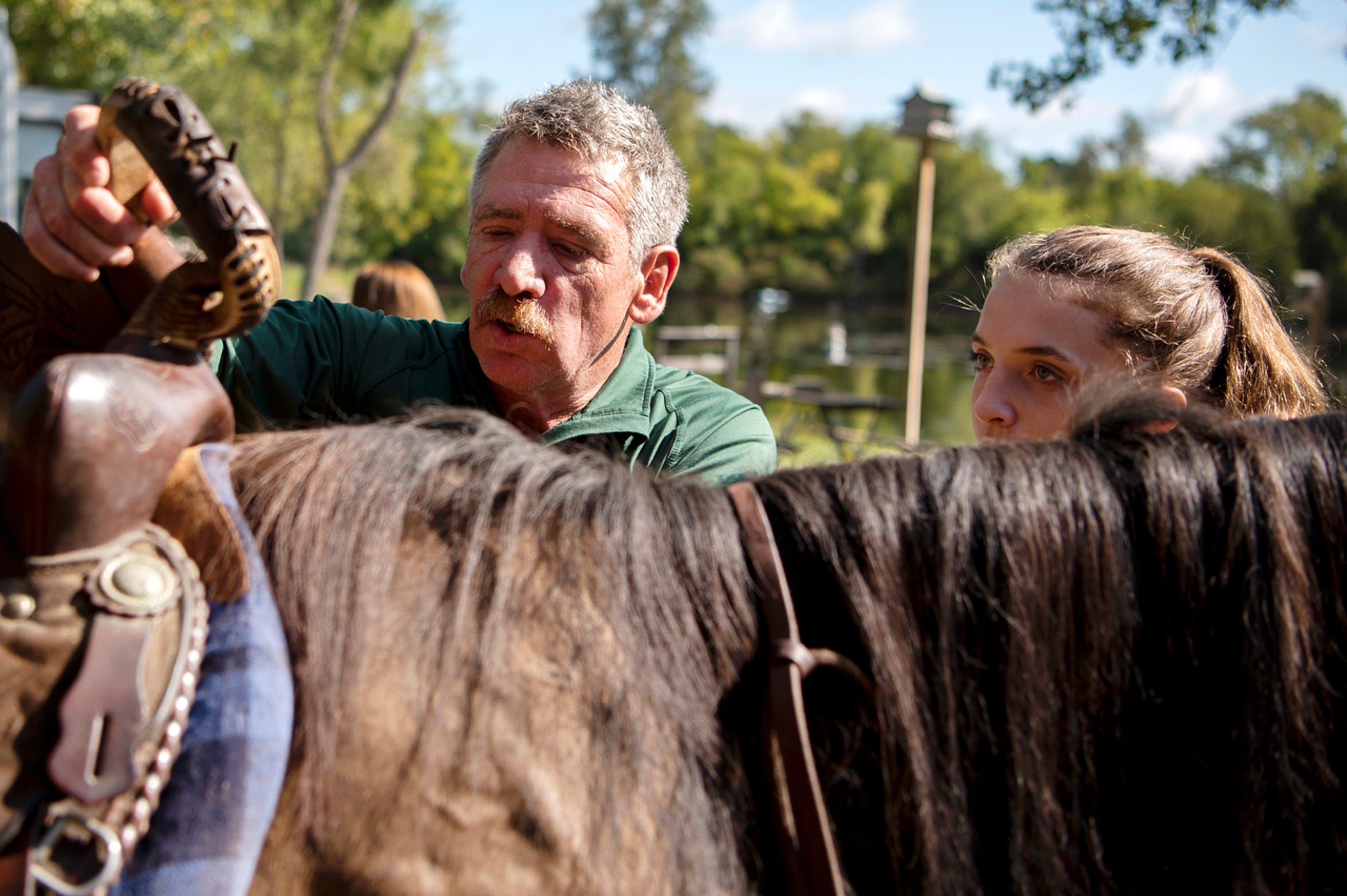 Jeff Friend assists Emmi Elkins, 14, on Saturday, Sept. 7, 2019 at Hidden Ponds Horse Rescue in Coldwater, Mich. At Hidden Ponds, rescued horses are used for therapy, giving horses and humans a second chance.