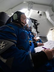 NASA astronaut Mike Fincke works through a check list inside a mockup of Boeing's CST-100 Starliner during a simulation at NASA's Johnson Space Center on Aug. 21, 2019.
