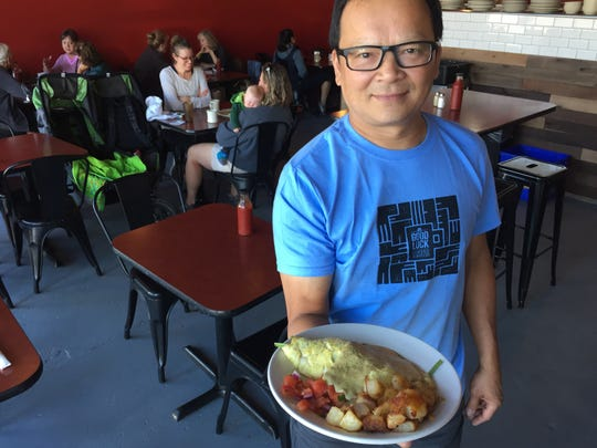 Jake Tran, owner of the Firebird Cafe, displays a spinach-and-red-onion omelet at the Essex Junction restaurant Sept. 10, 2019.