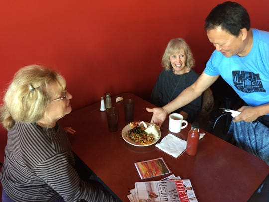 Firebird Cafe owner Jake Tran serves a chorizo migas plate to Janet Jaffe, left, of Westford, and Pam Keyser of Tunbridge at the Essex Junction restaurant Sept. 10, 2019.