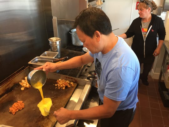 Owner Jake Tran and manager Andrea Pomainville work in the kitchen at the new Firebird Cafe location in Essex Junction on Sept. 10, 2019.