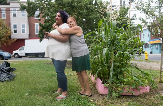 Jackie Santiago is hugged by her mother Maria Sierra as they stand by the North Camden lot that Santiago adopted and converted into a community garden with the help of neighborhood volunteers.  Santiago intended to purchase the lot but was out-bid and forced to move the urban oasis to a nearby, smaller lot.