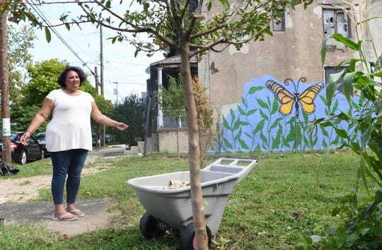 Jackie Santiago stands by the North Camden lot that she adopted and converted into a community garden with the help of neighborhood volunteers.  Santiago intended to purchase the lot but was out-bid and forced to move the urban oasis to a nearby, smaller lot.