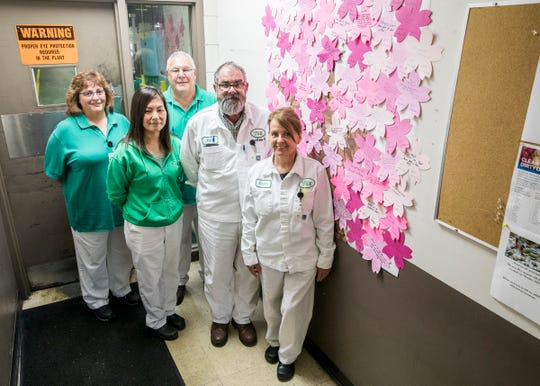 YSK Employees Ginger Short, Mary Stevens, Rick Tripp, Yukiko Essinger, and Kent Ziegler all stand beside the happiness cherry tree. Essinger had the idea for the tree where employees could write a happy memory at their time at the company with the tree looking more like a bush with so many responses.