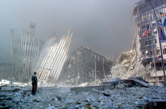 A man stands amid the rubble, calling out to see if anyone needs help, after the collapse of the first World Trade Center tower in New York on Sept. 11, 2001.