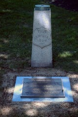 A plaque recounts the history of the true meridian markers near the Somerset County Historic Courthouse in Somerville.