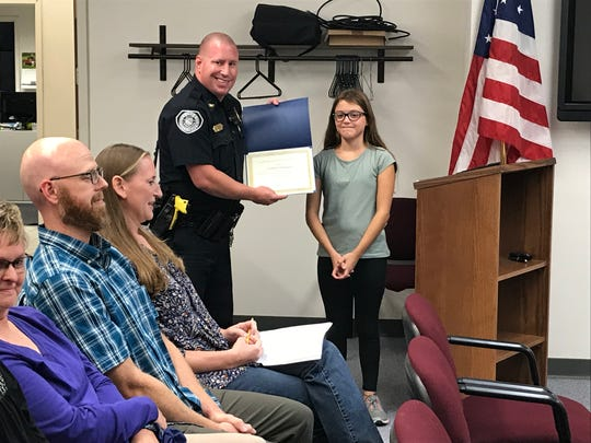 Carlisle Police Chief Matt Koch presents Sammi Dickson with a certificate of recognition after she gave him a petition to put Children at Play signs in her neighborhood.