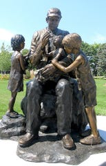 "A statue on the grounds of Blank Children's Hospital in Des Moines, by Dr. David Biehl, shows a volunteer giving the oral polio vaccine – the ""drops of life"" – to a child, with other children looking on."